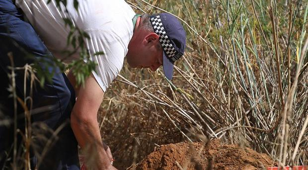 A British police officer checks soil samples during the search for evidence of Madeleine McCann