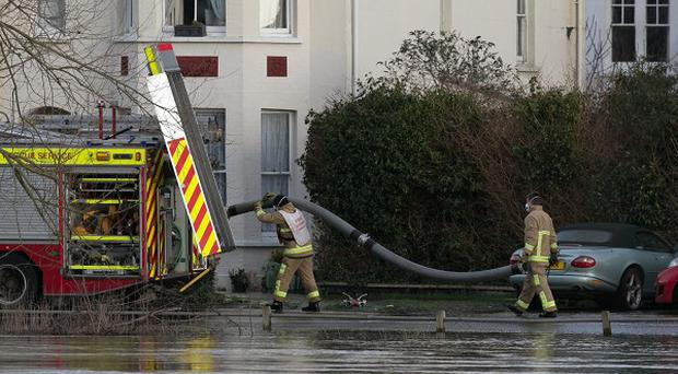 Firefighters at a house in Thameside in Chertsey, Surrey, where seven-year-old Zane Gbangbola died after suffering carbon monoxide poisoning when he fell ill in the flood-hit town