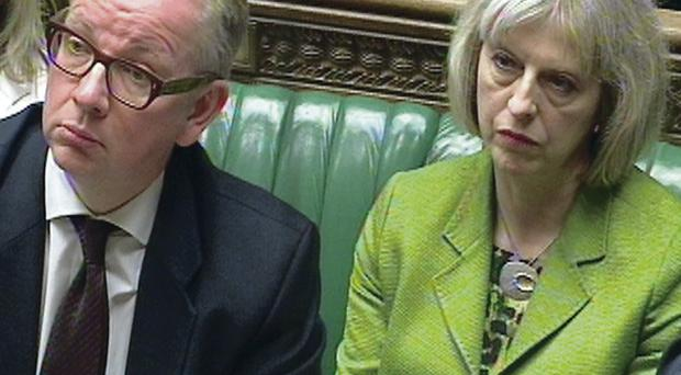 Michael Gove and Theresa May sit beside each other in the Commons yesterday