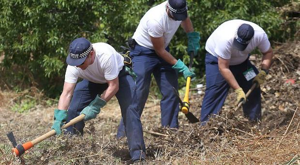 British police clear an area of wasteland during the search for evidence of Madeleine McCann in Praia da Luz