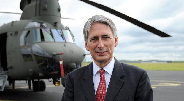 Defence secretary Philip Hammond stands in front of the new Chinook Mk6 helicopter during its unveiling at RAF Odiham in Hampshire