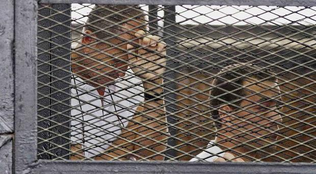 The Al Jazeera journalists appeared in a cage during their trial in Cairo (AP)