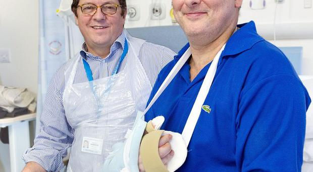 Professor Simon Kay (left) carried out the first hand transplant in the UK on Mark Cahill (right) last year (Leeds General Infirmary/PA)