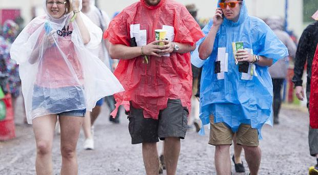 Festival goers shelter from the rain at the Glastonbury Festival