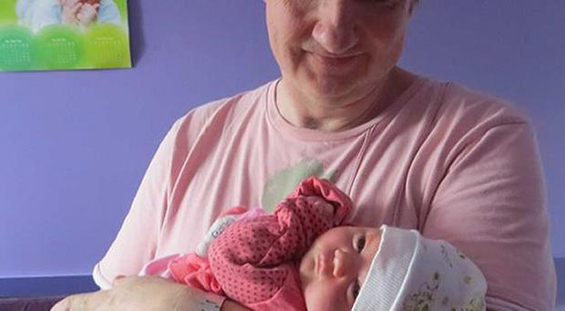 Grace in the arms of her father Nigel Griffiths, who fears he may have to leave his daughter in Georgia because of problems obtaining a passport