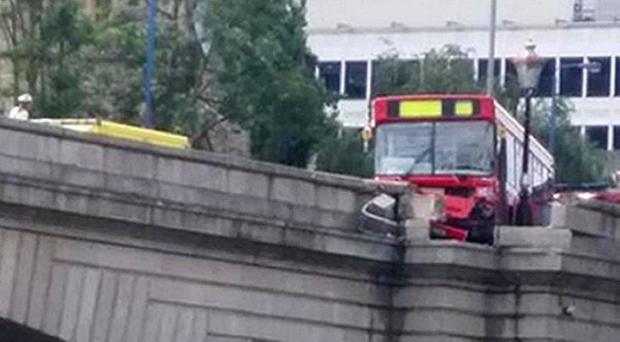 A passenger bus left hanging partly over the River Thames after an accident with a car at Putney Bridge, south west London.