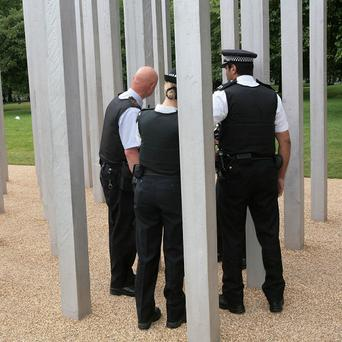 Police officers investigate the July 7 memorial which was defaced over the weekend