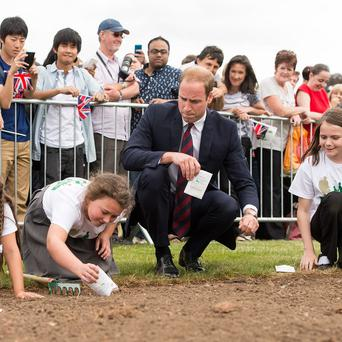 The Duke of Cambridge in his role as president of the Fields in Trust charity helps a class of pupils from Howes Primary School plant poppy seeds during a visit to Coventry's War Memorial Park