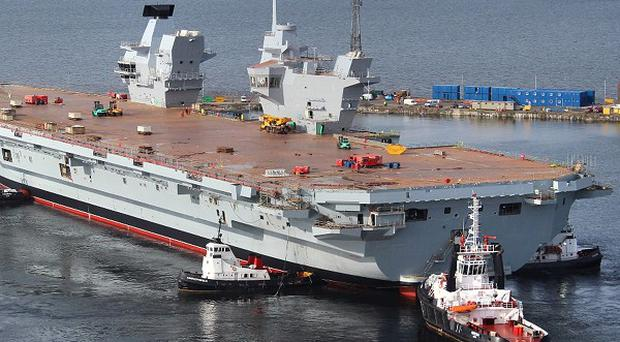 HMS Queen Elizabeth, the largest warship ever built in the UK, during her 'float out' of the dock at the Rosyth Dockyard in Fife, in which she was assembled for the first time. (BAE Systems/PA)