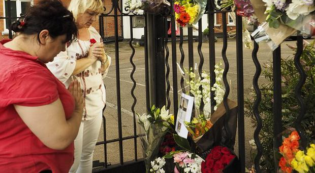 Two women pray at a shrine outside the Netherlands embassy in London for the victims in the Malaysian airlines crash