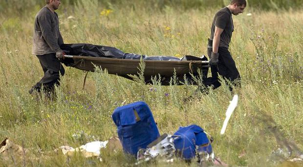 Emergency workers move the body of a victim at the crash site of Malaysia Airlines flight MH17 near the village of Hrabove, eastern Ukraine (AP Photo/Vadim Ghirda)