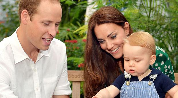 EDITORIAL USE ONLY This photo dated Wednesday July 2, 2014, was taken to mark Prince George's first birthday and shows the Duke and Duchess of Cambridge and the Prince during a visit to the Sensational Butterflies exhibition at the Natural History Museum, London.
