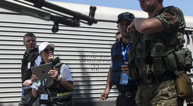 Deputy head of the OSCE mission to Ukraine Alexander Hug, background centre, accompanied by members of Netherlands' National Forensic Investigations Team guarded by armed pro-Russian fighters, walk on the platform as a refrigerated train loaded with bodies of the passengers departs from the station in Torez, eastern Ukraine (AP)