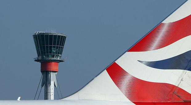 A British Airways plane passes the control tower at Heathrow Airport