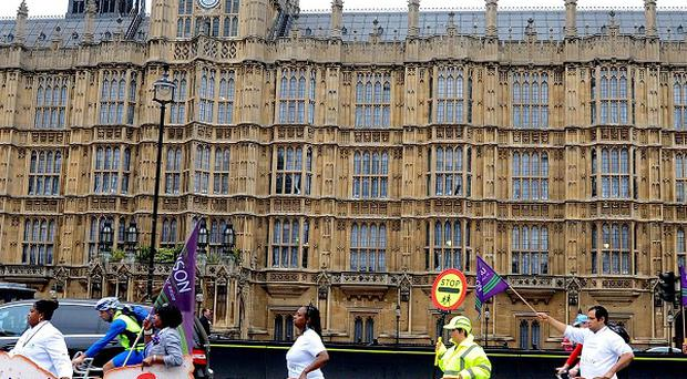 Public sector workers and members of the Unison union outside the Houses of Parliament during the last one-day walkout in a dispute over pay, pensions, jobs and spending cuts