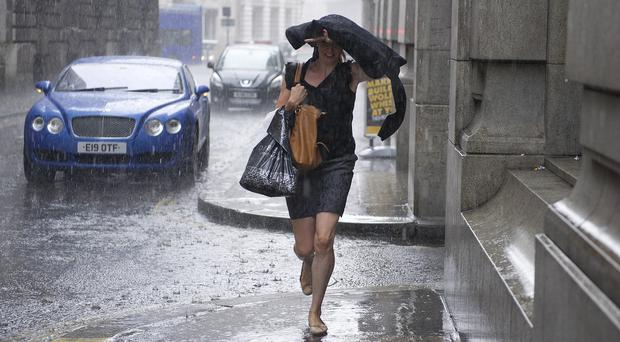 A woman runs as heavy rain falls in the City of London