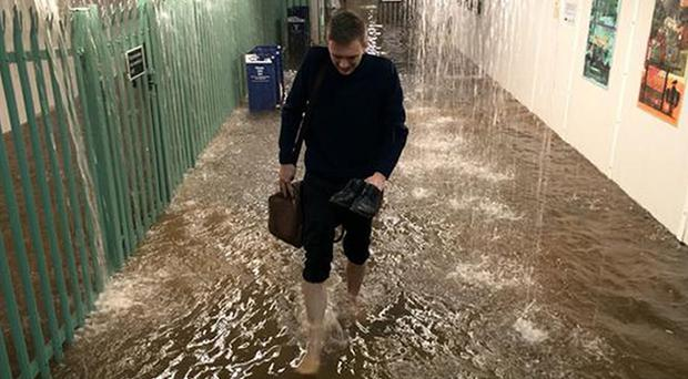 A commuter walks through a flooded Worthing train station underpass after storms hit the area (@travelsportcopy/PA)