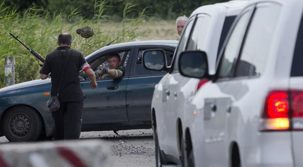A pro-Russian rebel throws a hat to his comrade as the convoy of the OSCE mission approaches near the village of Rassipne, Ukraine (AP)