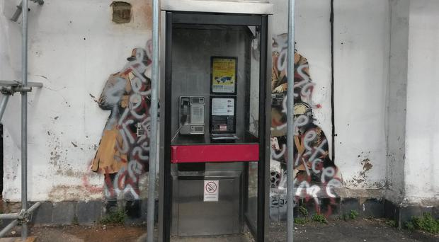 A Banksy mural which targets the issue of Government surveillance has been vandalised - with silver and red paint sprayed over it.