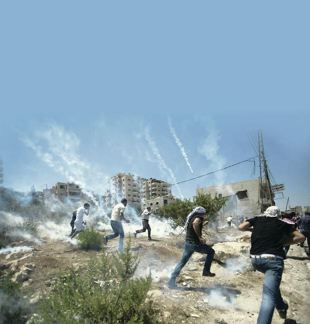 Palestinians run for cover during clashes with Israeli soldiers near Ramallah