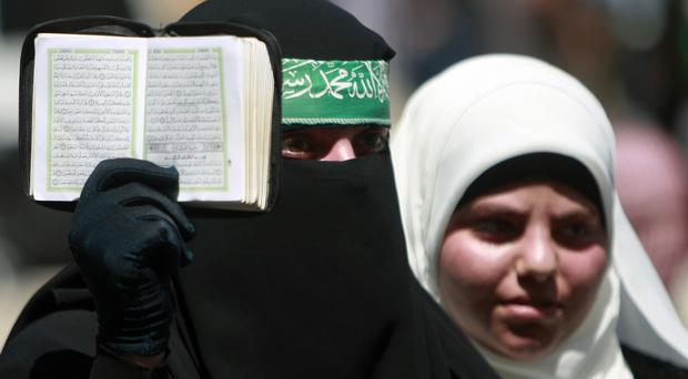 A Palestinian supporter of Hamas holds the Koran during a demonstration in the West Bank town of Tulkarem (AP)