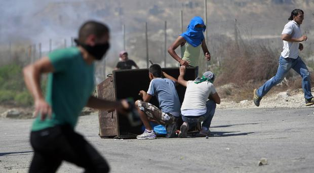 Palestinians run for cover from Israeli soldiers during clashes near the West Bank town of Tulkarem (AP)