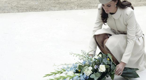 The Duchess of Cambridge lays a floral tribute at St Symphorien Military Cemetery in Mons, Belgium, yesterday