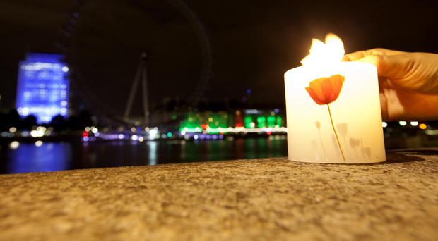 A candle is lit in London as the London Eye has it's lights switched off as part of the national campaign of remembrance, marking 100 years since Britain entered the First World War