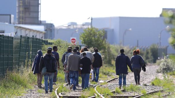 A group of migrants make their way through Calais, France, as tensions remain high following overnight clashes between rival groups waiting to try and cross the Channel to Britain.