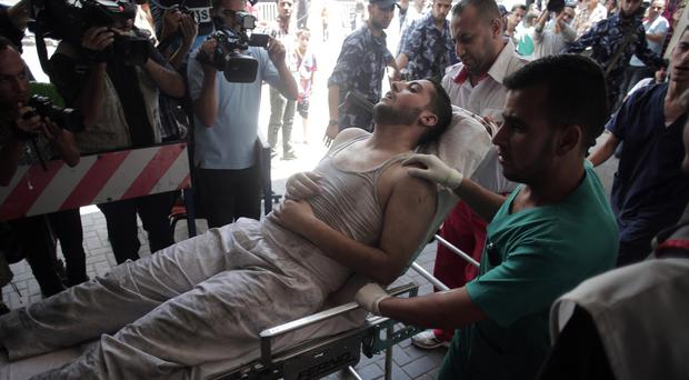 Palestinian medics wheel a wounded man on a stretcher into the Shifa hospital in Gaza City (AP/Khalil Hamra)
