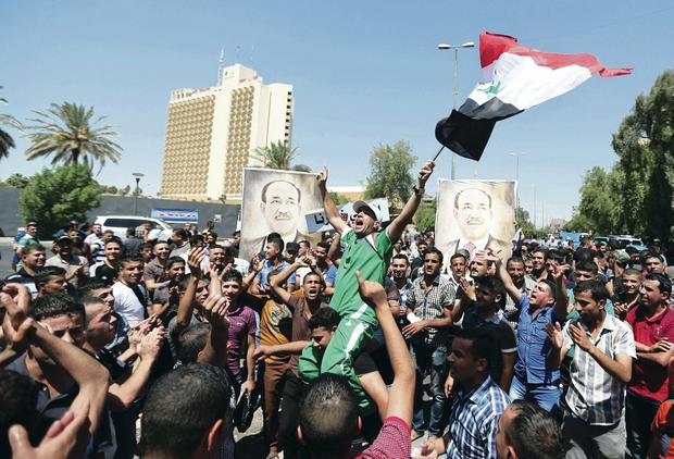 Iraqis rally in a show of support for embattled Prime Minister Nouri al-Maliki during a demonstration in Baghdad yesterday
