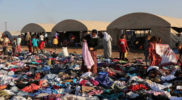 Displaced Iraqis from the Yazidi community look for clothes to wear among items provided by a charity organisation at the Nowruz camp, in Derike, Syria. (AP)