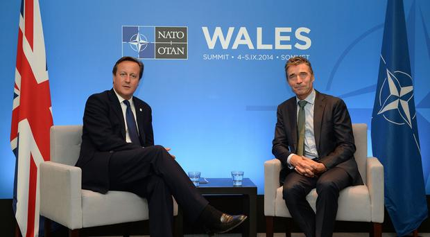 David Cameron, left, and Nato Secretary General Anders Fogh Rasmussen talk on the eve of the Nato Summit