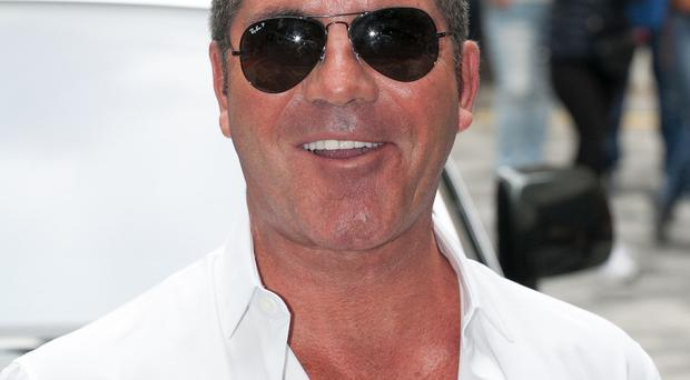 Simon Cowell admits he was embarrassed after his shirt button popped open during the arena auditions