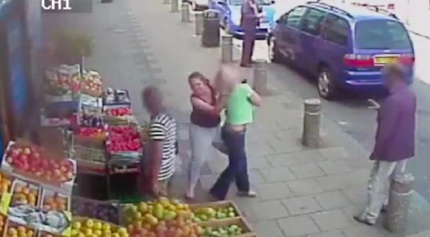 CCTV still of the moment a woman (black top) grabbed a female motorist and wrestled her to the ground outside a grocers in Birmingham's Handsworth Wood (West Midlands Police/PA)