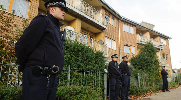 Police stand outside flats in south London after three women who were allegedly held as slaves for at least 30 years were rescued