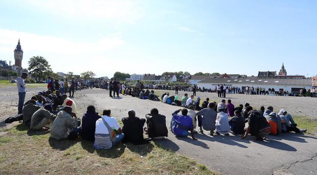 Migrants queuing for food at a feeding point in Calais