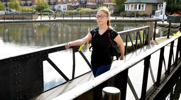 A police cadet walks across the bridge at Brentford Locks during reconstruction of the last known journey of Alice Gross