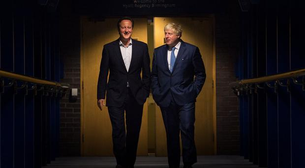 Prime Minister David Cameron and London Mayor Boris Johnson walk through the ICC in Birmingham on their way to an event during the Conservative Party conference