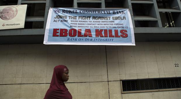 A woman walking past a poster to raise awareness of Ebola