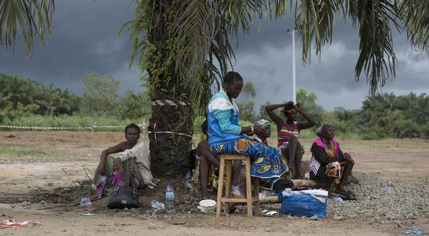 People suffering from the Ebola virus sit under a tree at Makeni Arab Holding Centre in Makeni, Sierra Leone (AP)