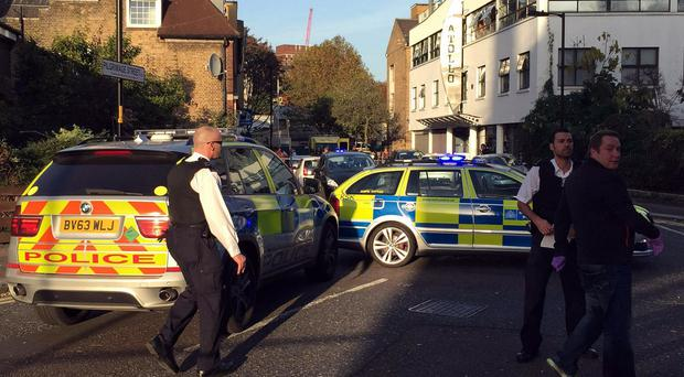 Police attend the scene where a teenager was stabbed to death