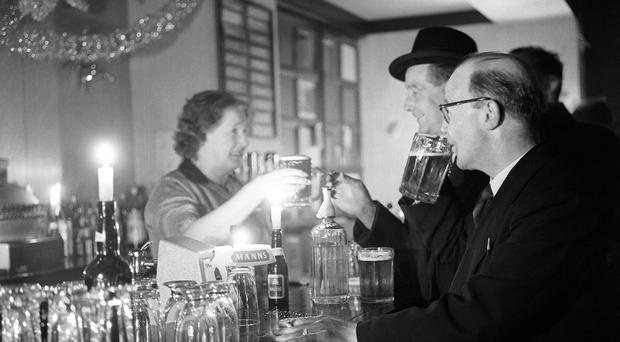 A customer at St Pancras station is served beer in candlelight during a previous blackout