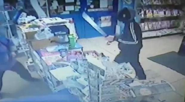 The attacker is seen entering Max and Sons in Sunderland wearing a balaclava and starts to wave the weapon (Northumbria Police/PA)