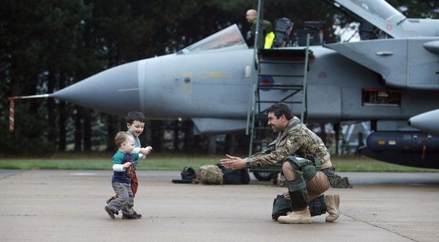 Squadron Leader Gareth Prendergast is greeted by his sons Hector and Felix upon returning to RAF Marham in Norfolk from Afghanistan