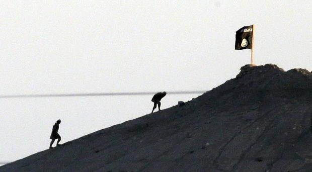 Islamic State militants planting their flag on a hilltop near the Turkey-Syria border (AP/file)
