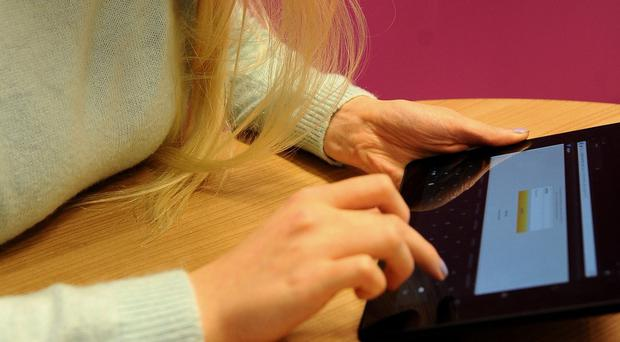 A woman using a Kindle Fire HDX 8.9 tablet.