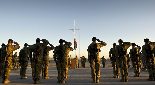 Garrison Sergeant Major WO Andrew Stephens (RAF) lowering the Union flag for the last time at Kandahar Airfield, Afghanistan (MoD)