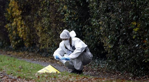 A forensics officer gathers evidence close to the scene in Fetcham, Surrey