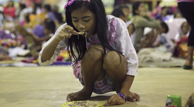 A resident eats at an evacuation centre in the aftermath of the typhoon. (AP)
